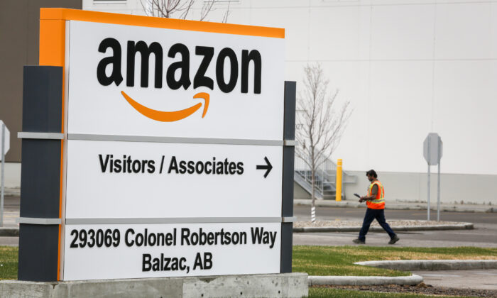 A worker walks past signage at an Amazon warehouse north of Calgary in Balzac, Alta. (Jeff McIntosh/The Canadian Press)