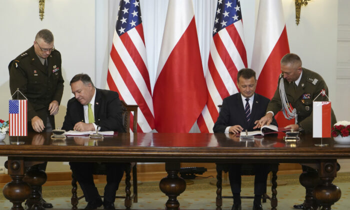 U.S. Secretary of State Mike Pompeo, left, and Poland's Minister of Defense Mariusz Blaszczak sign the U.S.–Poland Enhanced Defense Cooperation Agreement in the Presidential Palace in Warsaw, Poland, on Aug. 15, 2020. (Janek Skarzynski/Pool via AP)
