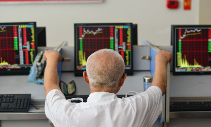 An investor looks at screens showing stock market movements at a securities company in Fuyang in China's eastern Anhui province on July 6, 2020. (STR/AFP via Getty Images)