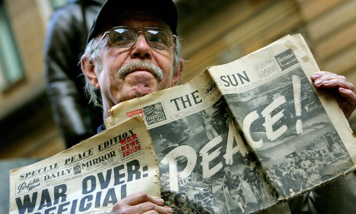 Collector John Sullivan displays two local newspaper front pages announcing the end of World War II during a service in Sydney, Australia on Aug. 15 2005. (Greg Wood/AFP via Getty Images)