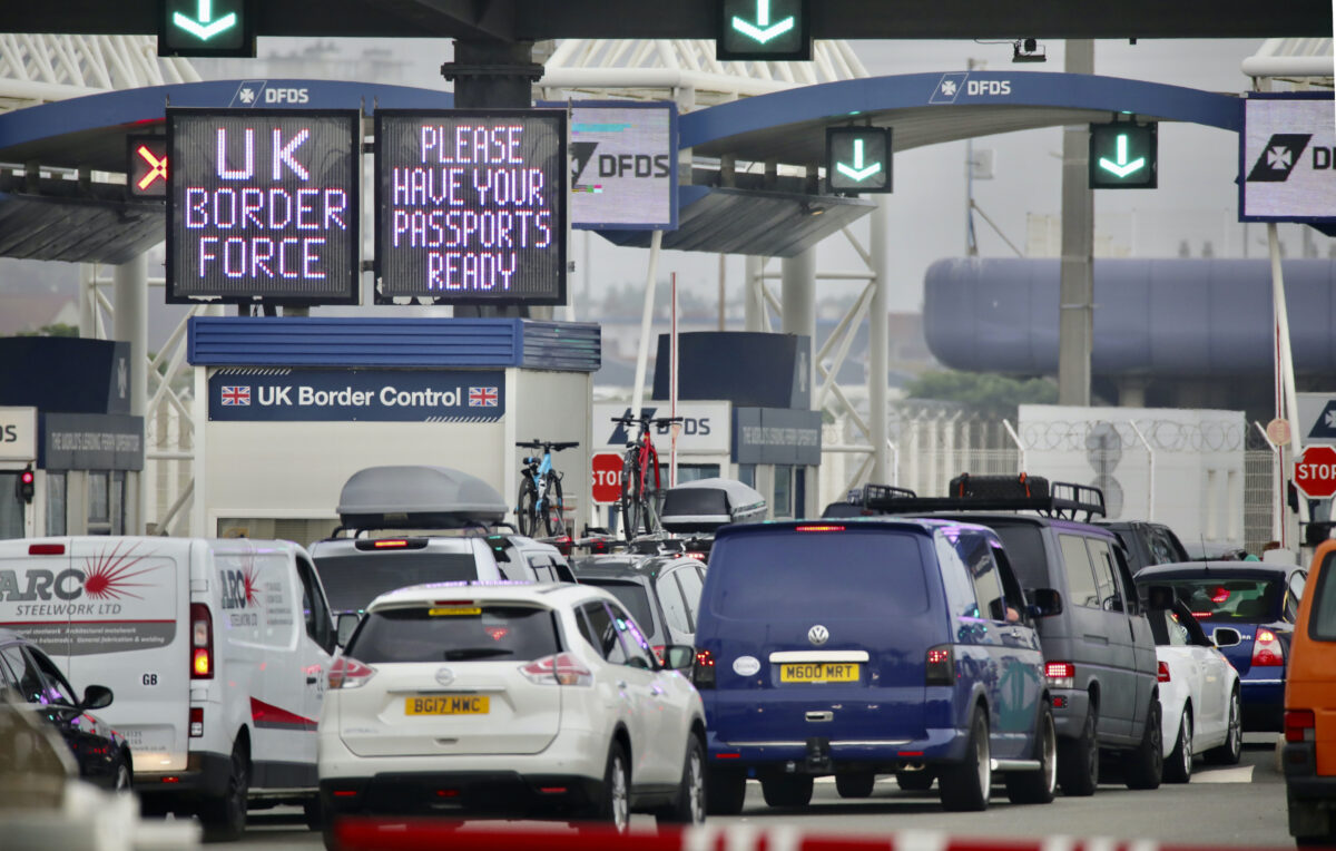 People queue in line to check-in for the cross channel ferry in Calais