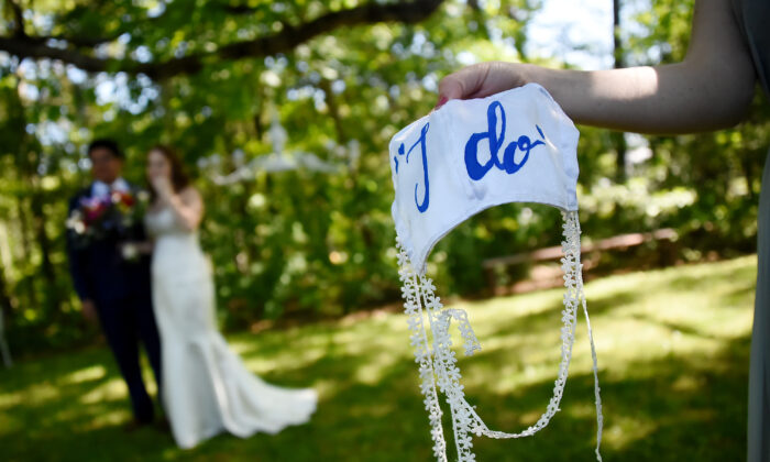 A bridesmaid holds on to the bride's face mask while newlyweds pose for pictures following their wedding ceremony in Rustburg, Va., on May 9, 2020. (Olivier Douliery/AFP/Getty Images)