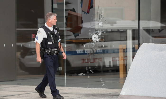 A Chicago police officer inspects an Apple store that was vandalized in Chicago on Aug. 10, 2020. (Kamil Krzaczynski/Reuters)