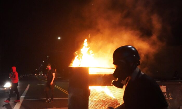 Rioters walk past a dumpster fire in Portland, Ore., on Aug. 14, 2020. (Nathan Howard/Getty Images)