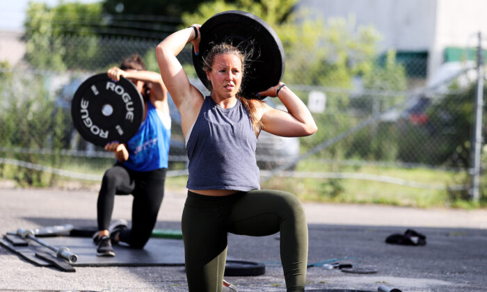 A woman holds a weight over her head during an outdoor fitness workout due to indoor gyms being ordered closed, in Oceanside, New York, on July 20, 2020. (Al Bello/Getty Images)