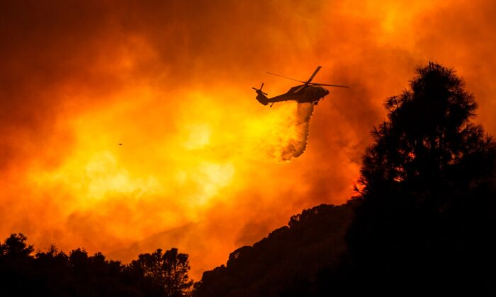A helicopter drops water on the Lake Hughes Fire in Angeles National Forest north of Santa Clarita, Calif., on Aug. 12, 2020. (Ringo H.W. Chiu/AP Photo)