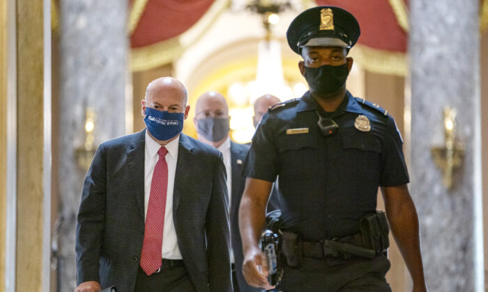 Postmaster General Louis DeJoy (L) is escorted to House Speaker Nancy Pelosi's office on Capitol Hill in Washington on Aug. 5, 2020. (Carolyn Kaster/AP Photo)