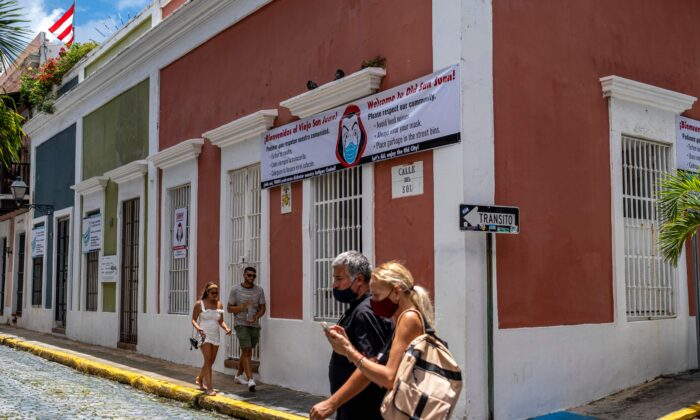 People walk pass by a banner urging visitors to wear face masks in San Juan, Puerto Rico, on July 20, 2020. (Ricardo Arduengo/AFP via Getty Images)