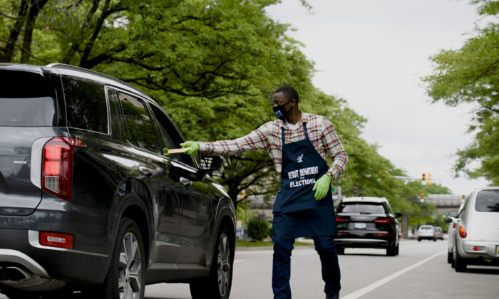 Election worker Demario Thurmond collects a sealed ballot curbside outside of the City of Detroit Department of Elections during the Michigan Primary Election in Detroit on Aug. 4, 2020. (Brittany Greeson/Getty Images)