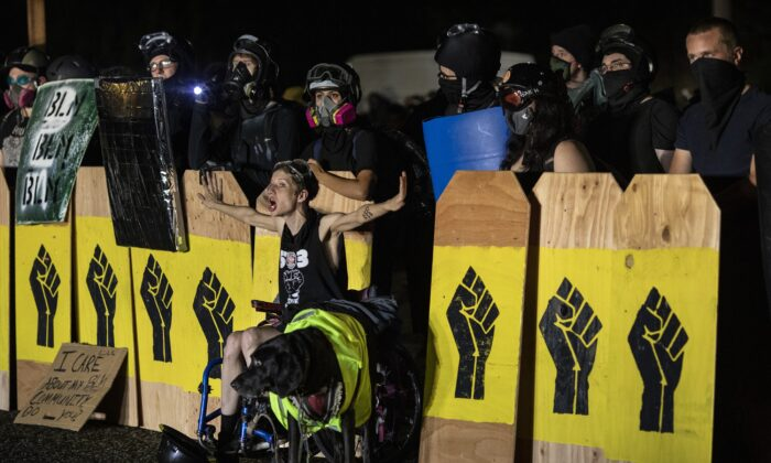 A woman screams at police as demonstrators hold signs emblazoned with a Black Lives Matter symbol in Portland, Ore., on Aug. 15, 2020. (Paula Bronstein/Getty Images)