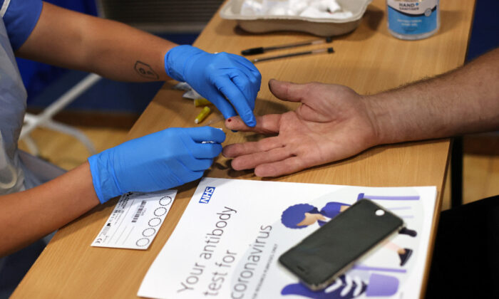 A worker takes a blood sample from a man during a clinical trial of tests for CCP virus antibodies at Keele University in Keele, Britain, on June 30, 2020. (Reuters/Carl Recine)