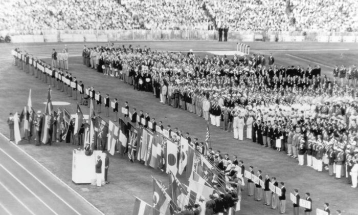 Australian athlete John Landy stands at the podium and takes the Olympic oath while athletes from competing nations hold their national flags during opening ceremonies for the Olympics, Melbourne, Australia, 26th November 1956. (Keystone/Hulton Archive/Getty Images)