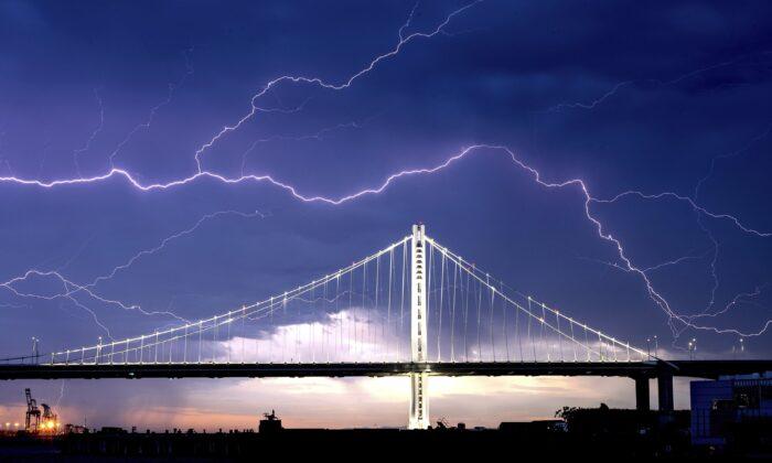 Lightning forks over the San Francisco-Oakland Bay Bridge as a storm passes over Oakland, Calif., on Aug. 16, 2020. (Noah Berger/AP Photo)