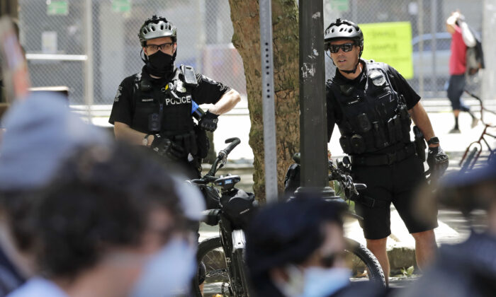 In this July 20, 2020, file photo, police officers look on at protesters in Seattle. (Elaine Thompson/AP Photo)