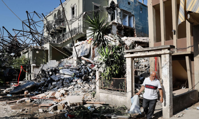A Lebanese man carries his belongings as he leaves his destroyed house near the scene where an explosion hit on Tuesday the seaport of Beirut, Lebanon on Aug. 6, 2020. (AP Photo/Hussein Malla)