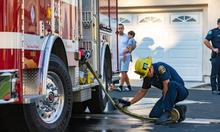 A firefighter with the Orange County Fire Department connects a hose to a truck while bystanders look on in Irvine, Calif., on Aug. 17, 2020. (John Fredricks/The Epoch Times)