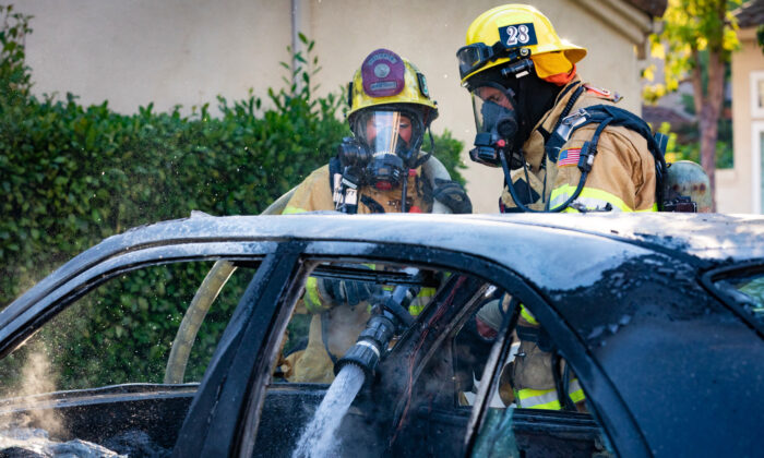 Firefighters from the Orange County Fire Department put out a blazing vehicle in Irvine,  Calif., on Aug. 17, 2020. (John Fredricks/The Epoch Times)