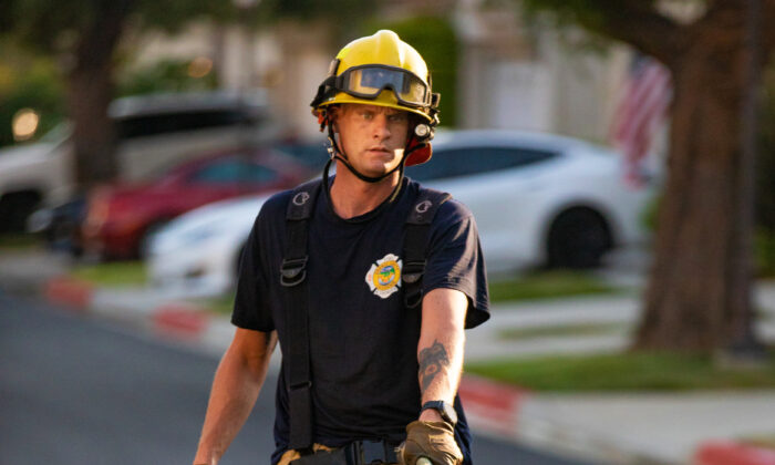 An Orange County firefighter carries a hose while responding to a burning car in Irvine, Calif., on Aug. 17, 2020. (John Fredricks/The Epoch Times)