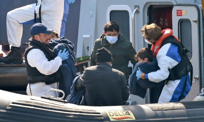 """UK Border Force officers help migrants with children, believed to have been picked up from boats in the Channel, disembark from Coastal patrol vessel """"HMC Hunter"""", in the port of Dover, on Aug. 9, 2020. (Glyn Kirk /AFP via Getty Images)"""