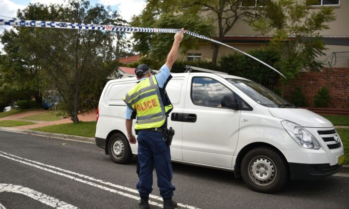 A policeman lets a van leave a street where a father shot dead his teenage son and daughter at their home in Sydney on July 6, 2018. (PETER PARKS/ Getty Images)