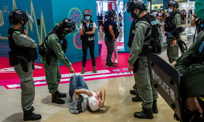 A riot police officer (2L) points at a woman lying down after being searched during a demonstration in a mall in Hong Kong on July 6, 2020, in response to Beijing's new national security law. (Isaac Lawrence/AFP via Getty Images)