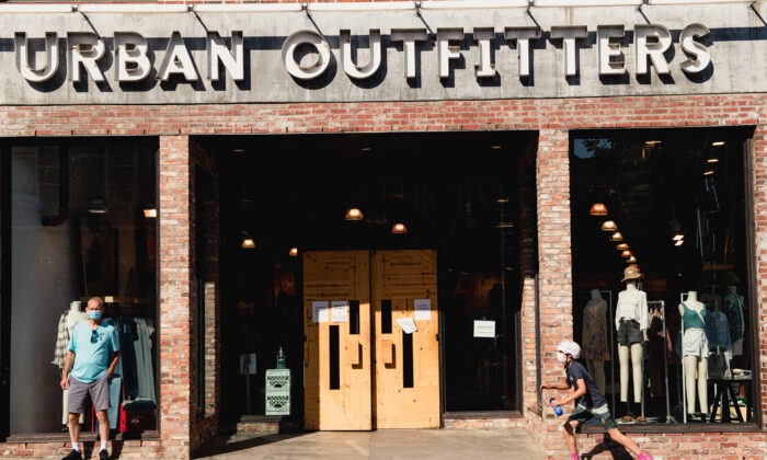 A person wearing a protective mask rides a skateboard past an Urban Outfitters store in downtown Asheville, N.C., on Wed., July 15 2020. (George Etheredge/Bloomberg via Getty Images )