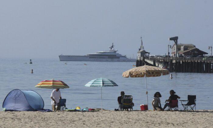 Early beachgoers secure spots on the shore at Santa Barbara, Calif., on Aug. 16, 2020. (AP Photo/John Antczak)