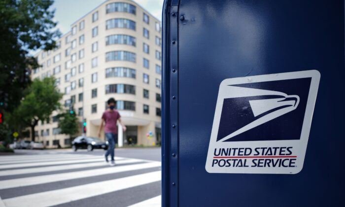 A man crosses an intersection next to a US Postal Service mailbox in Washington on Aug. 17, 2020. (Mandel Ngan/AFP via Getty Images)