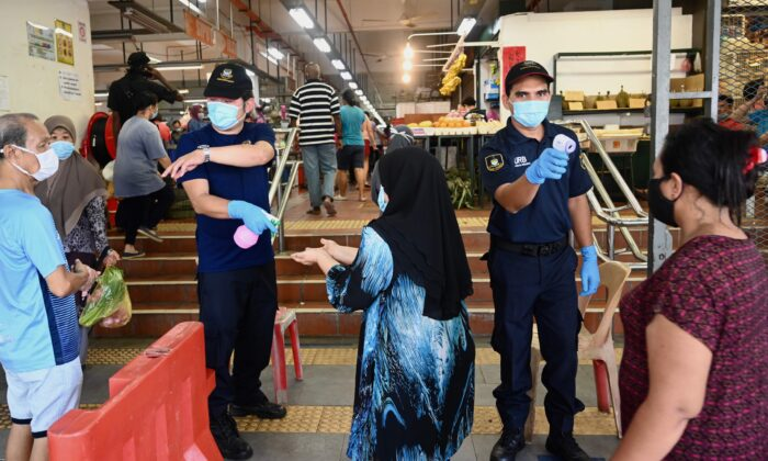 Security personnel check the temperatures of people entering a market, while enforcing social distancing, in Penang, Malaysia, on May 29, 2020. (Goh Chai Hin/AFP via Getty Images)