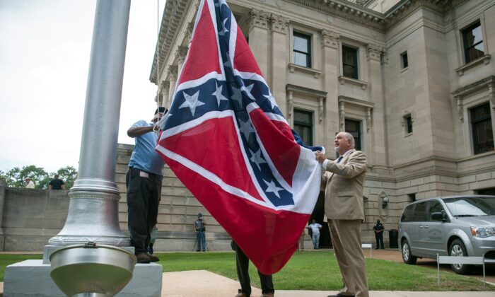 The state flag is raised for the flag retirement ceremony at the Mississippi State Capitol building in Jackson, Mississippi on July 1, 2020. (Rory Doyle/AFP via Getty Images)