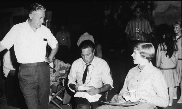 "(L–R) Director Robert Wise, Canadian actor Christopher Plummer, and British actress Julie Andrews talk on the film set of ""The Sound of Music,"" 1965. (Photo by Hulton Archive/Getty Images)"