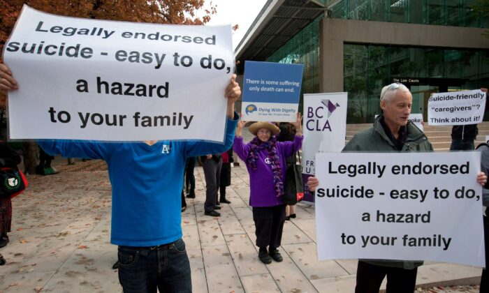 A woman (C) holds a sign in support of assisted suicide while others demonstrate against it outside the B.C. Court of Appeal on Oct. 10, 2013. (The Canadian Press/Darryl Dyck)