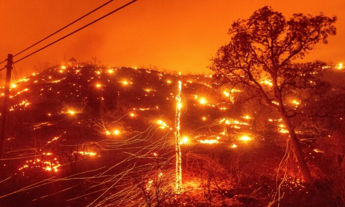 Seen in a long exposure photograph, embers burn along a hillside as the LNU Lightning Complex fires tear through unincorporated Napa County, Calif., on Tues., Aug. 18, 2020. Fire crews across the region scrambled to contain dozens of wildfires sparked by lightning strikes as a statewide heat wave continues. (Noah Berger/AP Photo)
