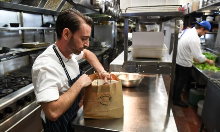 Chef packs a take-away meal in the kitchen of French restaurant France-Soir in Melbourne on May 8, 2020. (William West/AFP via Getty Images)