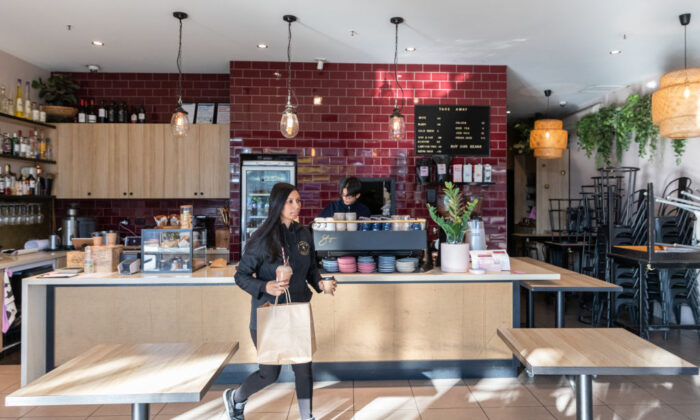 Nerissa Jayasingha owner of cafe Lankan Tucker carrying a takeaway order to give to customers who wait outside once they have ordered their food in Melbourne, Australia on July 9, 2020. (Asanka Ratnayake/Getty Images)