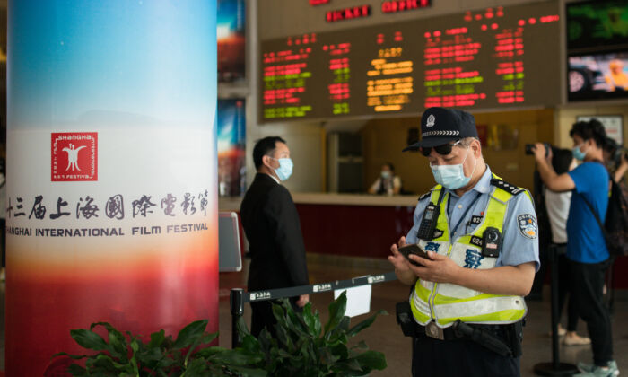 A police officer looks at his cell phone at Shanghai Film Center (SFC) in Shanghai on July 25, 2020. (Yifan Ding/Getty Images)