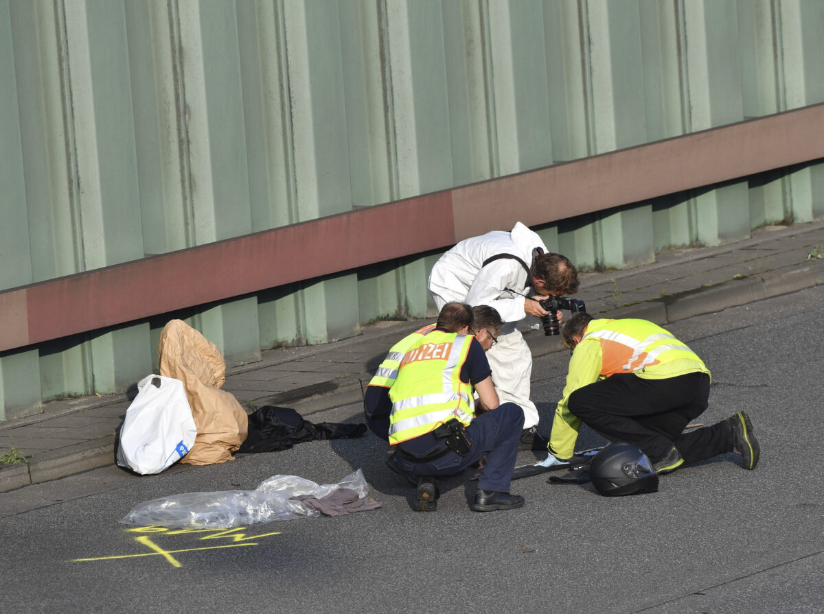 Police officers investigate on the city motorway A100