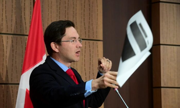 Conservative MP Pierre Poilievre throws a redacted document tabled at the House of Commons Finance Committee provided by the Government during a press conference on Parliament Hill in Ottawa on Aug. 19, 2020. (Sean Kilpatrick/The Canadian Press)