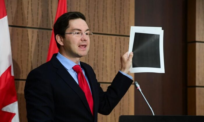 Conservative MP Pierre Poilievre holds up redacted documents during a press conference on Parliament Hill in Ottawa on Aug. 19, 2020. The documents were tabled by the Government at the House of Commons Finance Committee. (Sean Kilpatrick/The Canadian Press)