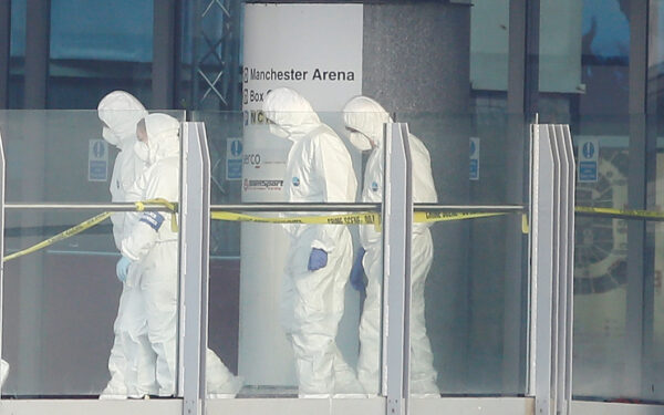 forensics investigators working at the entrance of the Manchester Arena,