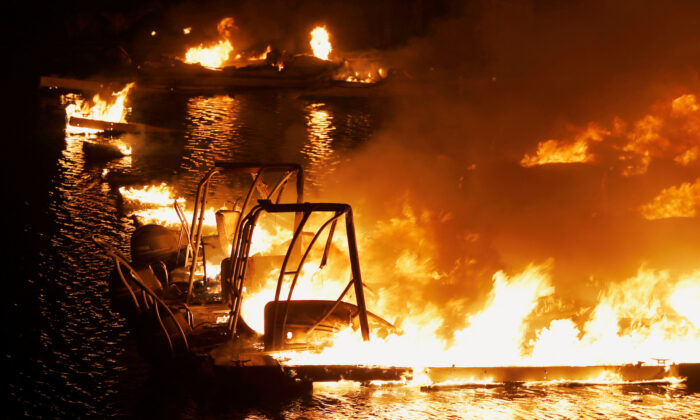 Boats engulfed in flames are seen at a dock near Markley Cove Resort during the LNU Lighting Complex Fire on the outskirts of Napa, Calif., on Aug. 19, 2020. (Stephen Lam/Reuters)
