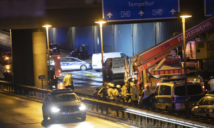 Forensic experts are investigating a car at the city motorway A100 after an accident in Berlin on Aug. 18, 2020. (Paul Zinken/dpa via AP Photo)