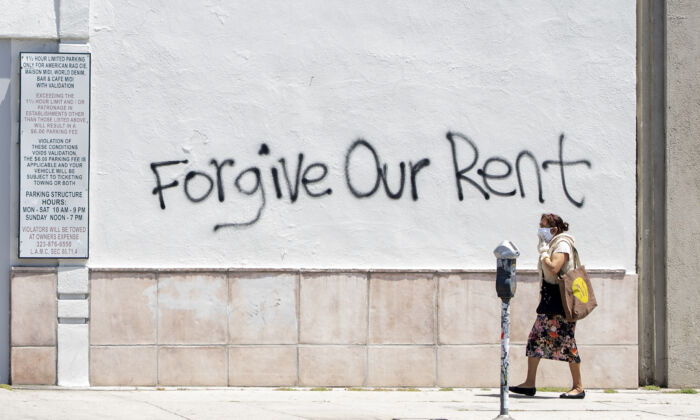 A woman wearing a mask walks past a wall bearing a graffiti asking for rent forgiveness on La Brea Ave. in Los Angeles, Calif. on May 1, 2020. (Valerie Macon/AFP via Getty Images)