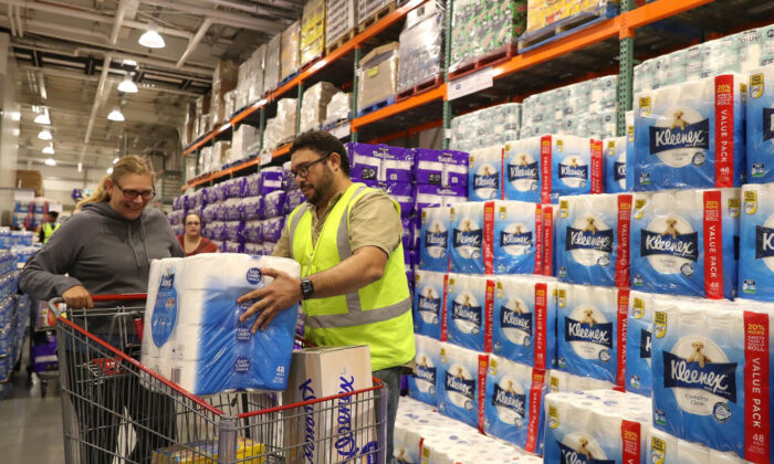 Staff members assist shoppers at Costco Perth on March 19, 2020 in Perth, Australia. (Paul Kane/Getty Images)