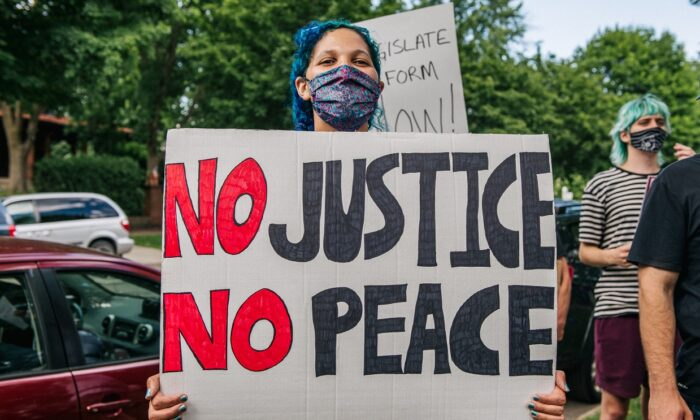 "A woman stands with a sign that reads ""No Justice No Peace"" during a demonstration in St. Paul, Minn., on June 24, 2020. (Brandon Bell/Getty Images)"