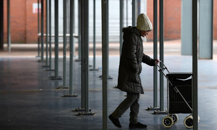 A woman pushes a shopping trolley through a closed market during the nationwide lockdown due to the CCP virus pandemic, in Manchester, England, on May 1, 2020. (Photo by Oli Scarff/AFP via Getty Images)