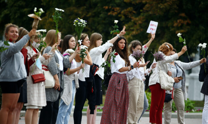 Women hold flowers while lining up during a demonstration against violence following recent protests to reject the presidential election results in Minsk on Aug. 20, 2020. (Vasily Fedosenko/Reuters)