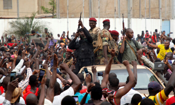 A crowd of people cheer Malian army soldiers at the Independence Square after a mutiny, in Bamako, Mali on Aug. 18, 2020. (Moussa Kalapo/Reuters)