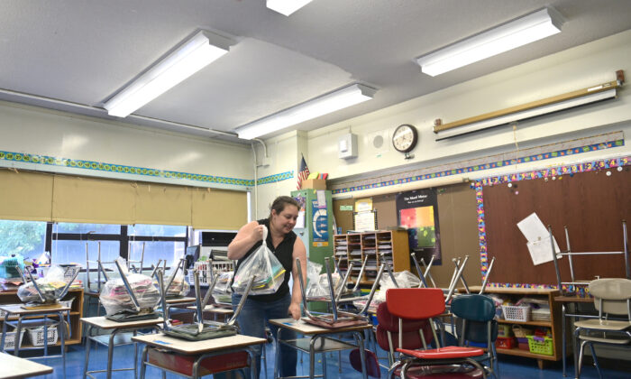 A teacher at Yung Wing Elementary School moves desks and chairs in her classroom to socially distance desks for the 2020-21 school year in New York City, N.Y., on Aug. 17, 2020. (Michael Loccisano/Getty Images)