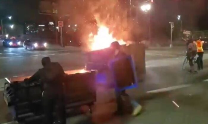 Rioters push flaming dumpsters in Portland, Ore., on Aug. 19, 2020. (Reuters)